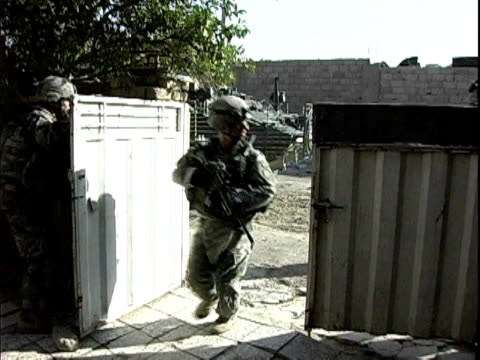 army soldiers running into fenced compound after taking sniper fire/ baghdad, iraq / audio - 記錄片鏡頭 個影片檔及 b 捲影像
