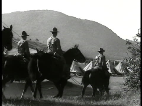 army soldiers setting up military pup tents in field. cavalry soldiers on horseback riding into large tent area. soldier helping soldier check gas... - 1935 stock-videos und b-roll-filmmaterial