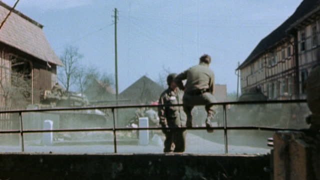 vidéos et rushes de army soldiers sitting on fence as jeep hauling trailer and a motorcycle pass, and army vehicles parked in side road as weapons carrier loaded with... - 1945
