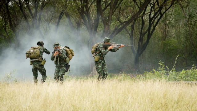 Army soldiers with guns during the military operation in the field, War concept