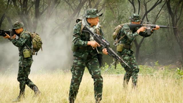 soldaten mit gewehren während der militäroperation im feld krieg konzept - war stock-videos und b-roll-filmmaterial
