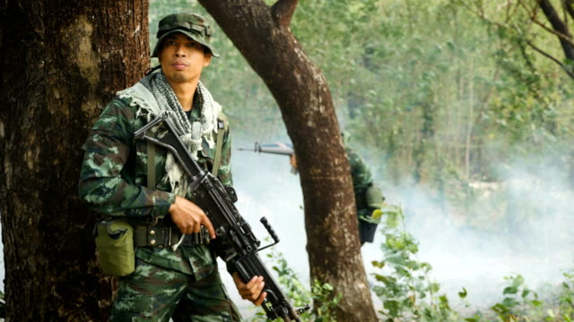 Army soldiers with guns during the military operation in the forest, War concept