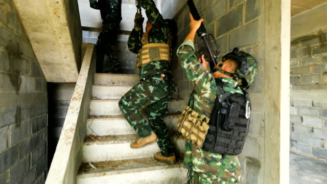 army soldiers with guns during the military operation in the abandoned building, war concept - special forces stock videos & royalty-free footage
