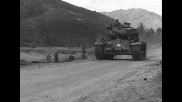 a us army tank approaches / a soldier fires a machine gun as another feeds bullets from a bandolier / note month/day not known - bandolier stock videos & royalty-free footage