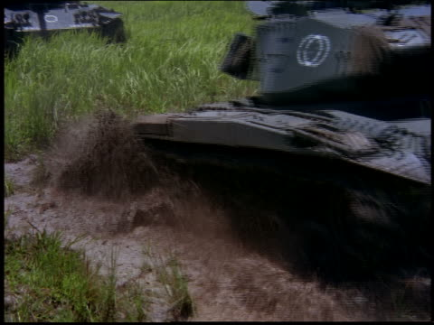 Army tanks moving through mud puddles in field toward camera / Rio de Janeiro, Brazil
