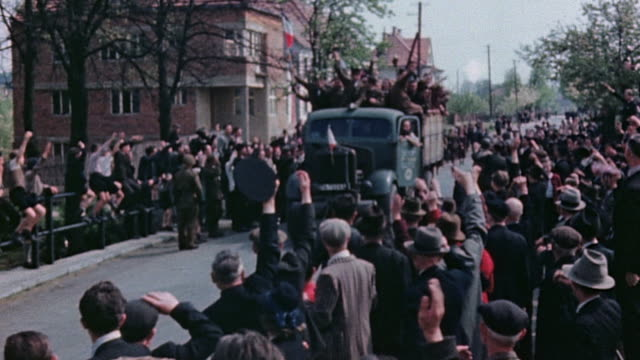 vidéos et rushes de s army truck loaded with liberated allied prisoners of war driving through waving crowd - prisonnier