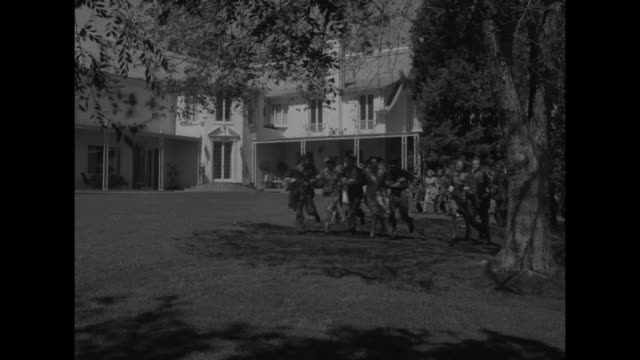 US Army truck pulling up in driveway of Mary Pickford's 'Pickfair' estate soldiers running up to it USO and volunteer hostesses are holding a party...