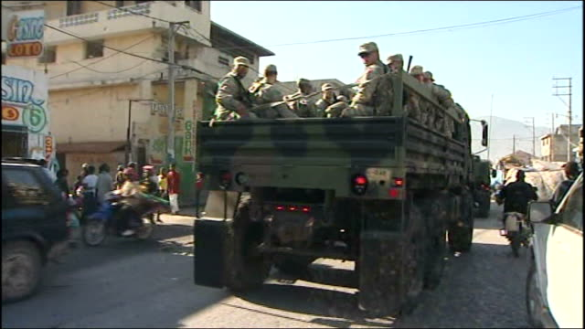 us army truck with soldiers in back along on road people on street as noise of gunshot heard sot haitian police with reporter to camera beside - haiti stock-videos und b-roll-filmmaterial