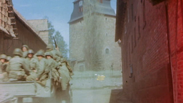 s army trucks loaded with soldiers driving through dusty village during world war ii european campaign / germany  - infanterie stock-videos und b-roll-filmmaterial