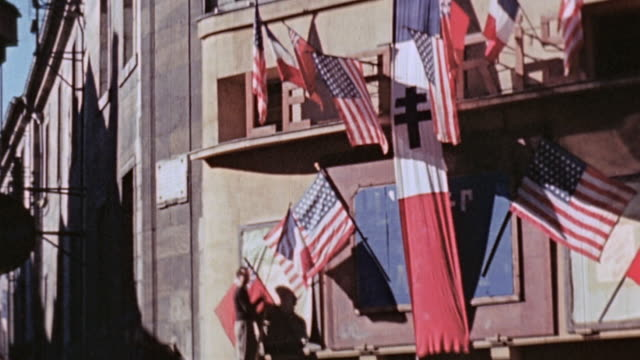 s army unit arriving in town decorated with american and french flags and bunting troops marching through and driving in m35 trucks / france - civilperson bildbanksvideor och videomaterial från bakom kulisserna
