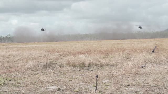 us army us marines and australian defense force conduct a combined joint force maneuver exercise with m142 high mobility artillery rocket system rbs... - アパッチヘリコプター点の映像素材/bロール