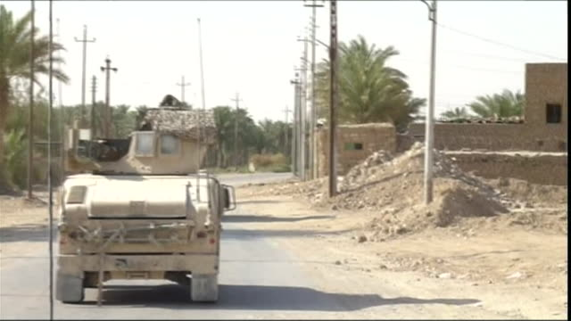 ms pov army vehicle stopping and soldier stepping out to talk to local man, haditha, al anbar, iraq - dish dash stock videos & royalty-free footage