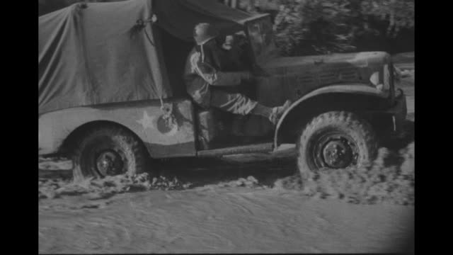 army willys mb jeep moves slowly through deep mud truck maneuvers across stream and onto mud on the other side two men in jeep truck vehicle with men... - 四輪駆動車点の映像素材/bロール
