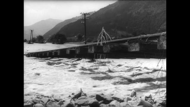vídeos de stock, filmes e b-roll de arno river flooding in austria / high waters rush through the valley / train tracks half submerged / street signs with poles half visible and rushing... - high street