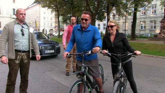 arnold schwarzenegger sighted riding a bike with heather milligan on september 27, 2016 in munich, germany. - arnold schwarzenegger stock-videos und b-roll-filmmaterial