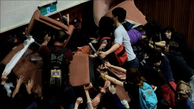 Around 200 students and activists break through a security barrier and take over the main chamber in Taiwan's parliament singing and dancing in...