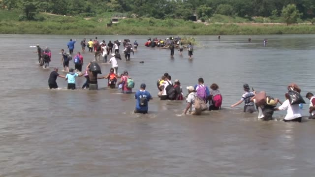 stockvideo's en b-roll-footage met around 2000 migrants who are part of a caravan that came from el salvador cross from guatemala into mexico through the suchiate river after trying to... - grens