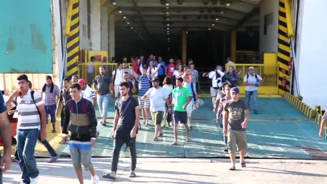 around 2500 refugees including mostly syrians wait to get on the buses after got off from the anek lines' passenger ship 'eleftherios venizelos'... - 2015 stock-videos und b-roll-filmmaterial