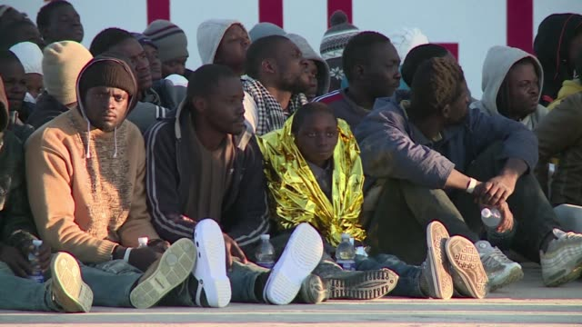 around 600 migrants from sub saharan africa disembark in augusta port in sicily where they are given shoes and water by the red cross and undergo... - zoll und einwanderungskontrolle stock-videos und b-roll-filmmaterial