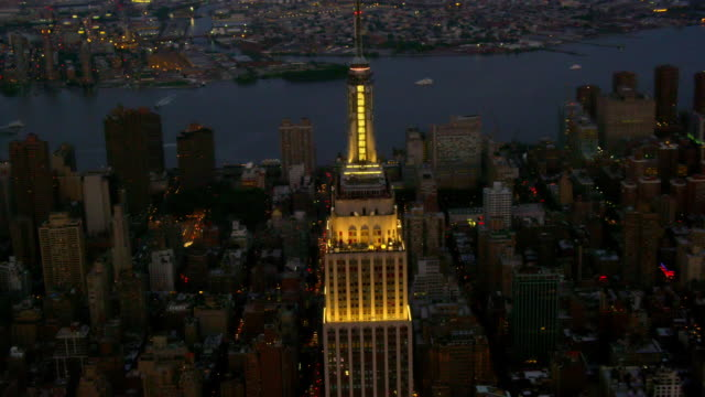 CLOSE UP AERIAL around Empire State Building and surrounding buildings at dusk