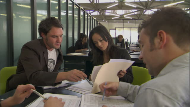ms pan around four people having meeting at table in office/ sydney, australia - ペン点の映像素材/bロール