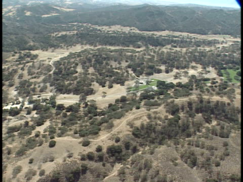 around michael jackson's neverland ranch estate, large area w/ trees stretching into distance, barely visible amusement park area. ca - ネバーランドバレーランチ点の映像素材/bロール