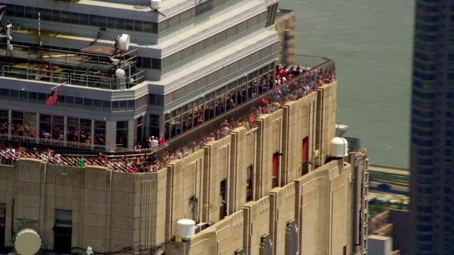 CLOSE UP AERIAL around observation deck of Empire State Building to MEDIUM SHOT Midtown Manhattan