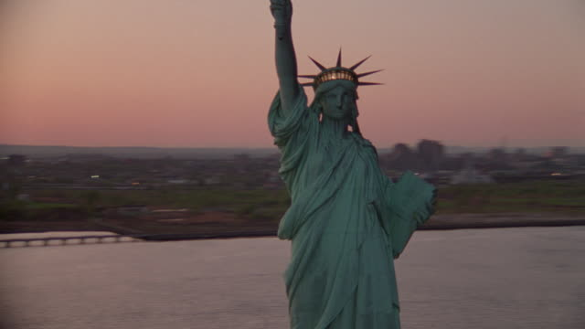 AERIAL around Statue of Liberty at twilight