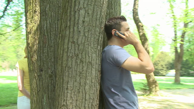 vidéos et rushes de ms pan around tree in park as man and woman lean on opposite sides and talk on mobile phones/ - s'appuyant