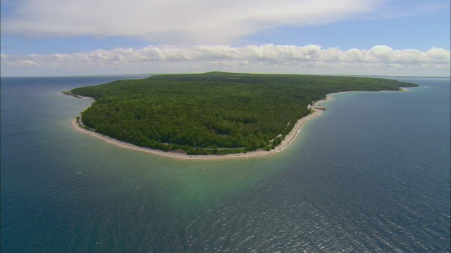 aerial around tree lined beach at northern tip of mackinac island state park with clouds and horizon/ mackinac island, michigan - upper peninsula stock videos & royalty-free footage