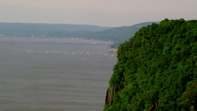 LONG AERIAL POV around tree-covered cliff toward boats on water and waterfront buildings and marina