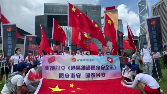 around two dozen pro-china supporters rally near hong kong's government headquarters in support of a sweeping national security law passed by beijing... - dozen stock videos & royalty-free footage