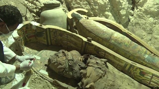 vídeos de stock, filmes e b-roll de arqueologos egipcios desenterraron varias momias coloridos sarcofagos de madera y mas de mil estatuas funerarias de una tumba de 3500 anos de... - madera material