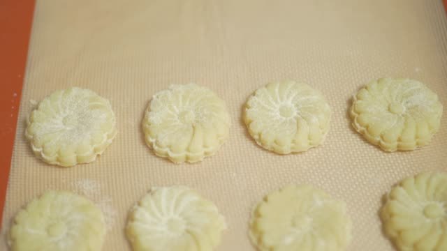 arrange  shortbread on parchment for baking in home kitchen - parchment stock videos & royalty-free footage