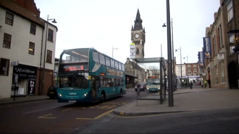 arriva faces court action over disability; t26031248 / darlington: bus along street - darlington north east england stock videos & royalty-free footage
