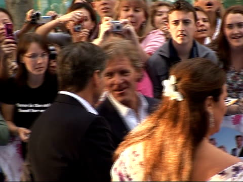 arrivals at 'mamma mia' film premiere pierce brosnan signing autographs for fans and along/ brosnan drinking bottle of water - mamma mia stock videos and b-roll footage