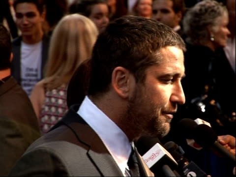 Arrivals for 'RocknRolla' film premiere Gerard Butler interviewed on red carpet with actress Thandi Newton in background