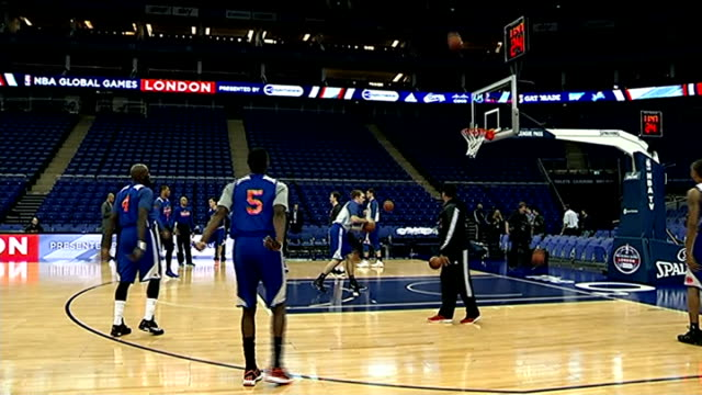 London INT New York Knicks players standing together saying 'NBA' SOT Basketball into hoop Basketball players practicing on court Player shooting at...