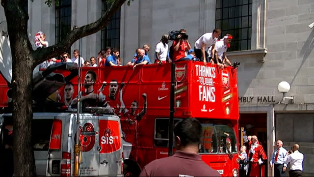 Arsenal FA Cup victory parade **Pop Music heard over following** Per Mertesacker waving from top of bus as holding FA Cup trophy/ Arsenal opentop bus...