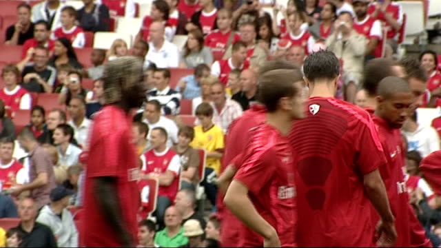arsenal players at open training session england london emirates stadium ext arsene wenger walking along pitch waving to fans and chatting with... - イズリントン点の映像素材/bロール