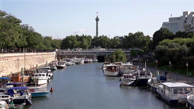 vídeos de stock, filmes e b-roll de arsenal port in paris france where seine river and saintmartin canal link in the background the column of july at place de la bastille - bastille