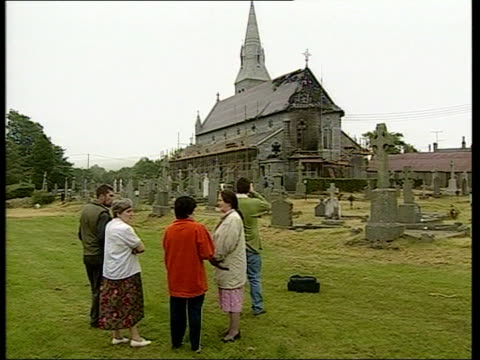 arsonists attack ten catholic churches; itn northern ireland: co antrim: crumlin int: tony blair being shown firebombed church by vicar tilt up hole... - irvine video stock e b–roll