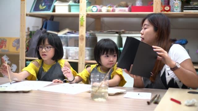 art class teacher teaching asian chinese children painting in art studio - art class stock videos & royalty-free footage