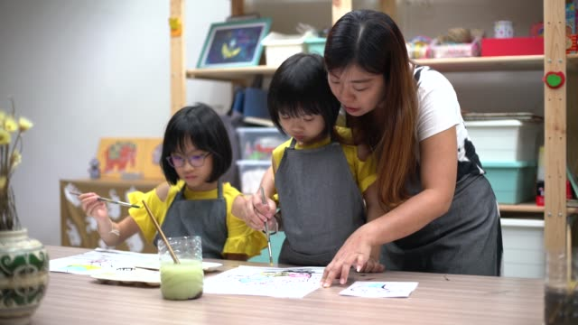 art class teacher teaching asian chinese children painting in art studio - art studio stock videos & royalty-free footage