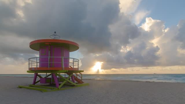 vídeos de stock, filmes e b-roll de art deco style lifeguard hut on south beach, ocean drive, miami beach, miami, florida, usa - night to day time lapse - time lapse da noite para o dia