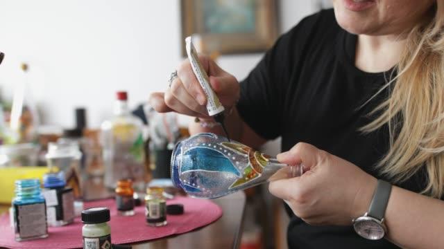 kunst malerei auf einer glasflasche - kunst, kultur und unterhaltung stock-videos und b-roll-filmmaterial