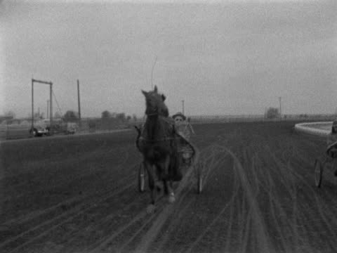 Art Shaw w/ whip in hand in horse sulky driving galloping horse on Walworth County Fairgrounds horse racing track WI