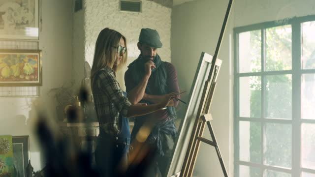 vidéos et rushes de instructeur et l'étudiant en art - toile à peindre
