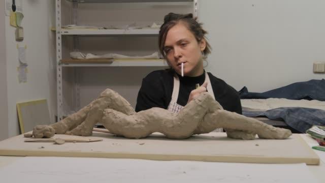 studio d'arte. giovane donna che fa una scultura. - pittore video stock e b–roll