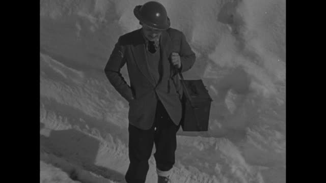 arthur menken paramount news cameraman wearing a helmet and standing in deep snow lights a cigarette for a norwegian soldier / note exact day not... - cameraman stock videos & royalty-free footage